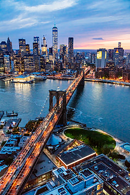 Aerial of lower Manhattan skyline and Brooklyn bridge at dusk, New York, USA - p651m2007424 by Matteo Colombo photography