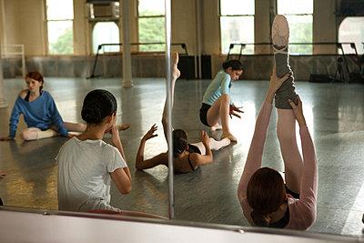 Ballet dancers warming up in dance studio - p9240137 by Carey Kirkella