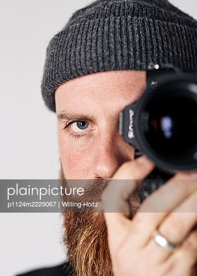 Mann mit Strickmütze fotografiert mit Digitalkamera - p1124m2229067 von Willing-Holtz