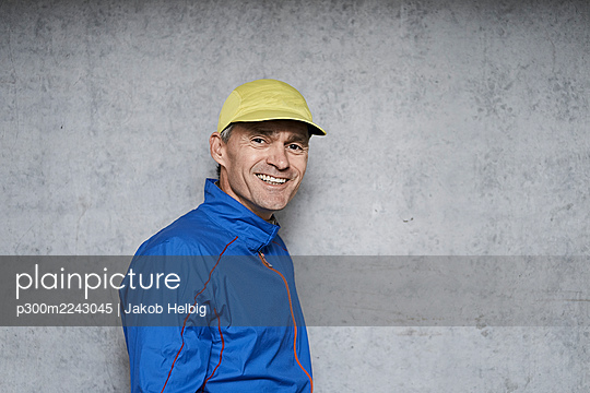 Happy mature man wearing cap standing by gray wall - p300m2243045 by Jakob Helbig