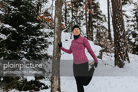 Woman stretching in winter forest - p312m2299723 by Plattform