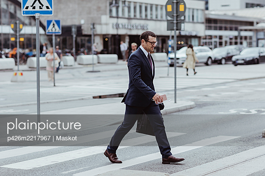 Businessman with bag crossing road in city - p426m2217967 by Maskot