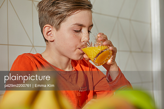 Boy sitting at breakfast table, drinking orange juice. - p429m2200761 by Emma Kim