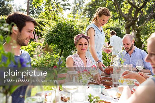 Essen mit Freunden im Garten - p788m1165351 von Lisa Krechting