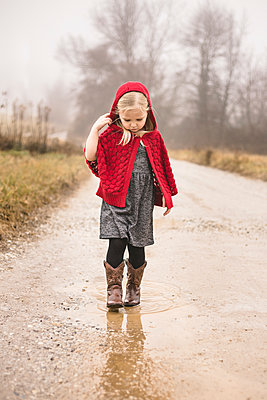 Girl in warm clothing walking on puddle - p1166m1526932 by Cavan Images