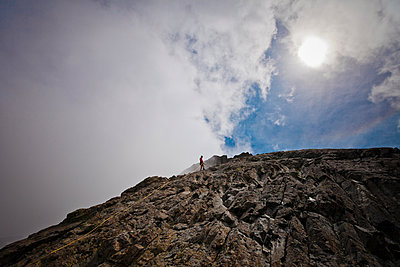 Mid distance view of hiker climbing rock formations against cloudy sky - p1166m1531496 by Cavan Images