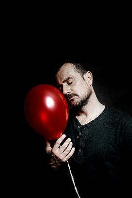 Man holding red balloon - p1521m2150065 by Charlotte Zobel