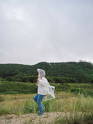 Girl with a raincoat runs on a sand dune among the vegetation - p1522m2100589 by Almag