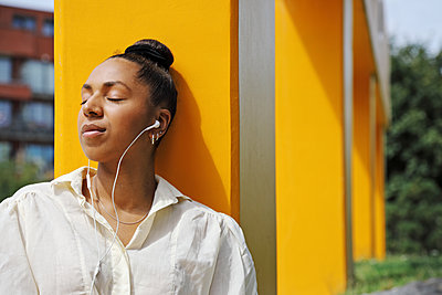 young woman listening to music through earbuds   - p1540m2110354 by Marie Tercafs