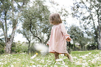 Little girl walking on flower meadow - p300m1587633 by Katharina Mikhrin