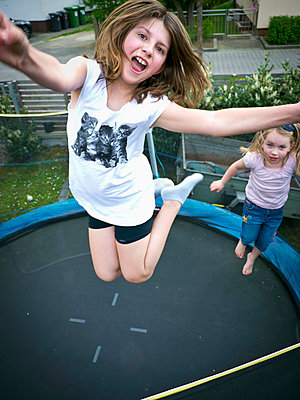 Germany, Bavaria, Two girls jumping on trampoline - p300m980082 by Leon Fischer