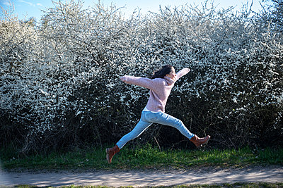 Cutting a caper in front of blackthorn - p310m2279011 by Astrid Doerenbruch