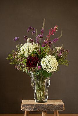 Glasvase mit natürlichem Blumenstrauß mit Hortensie vor brauner Wand auf Holzschemel. - p948m2134936 von Sibylle Pietrek