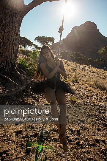 Brunette woman swings under tree - p1640m2264340 by Holly & John