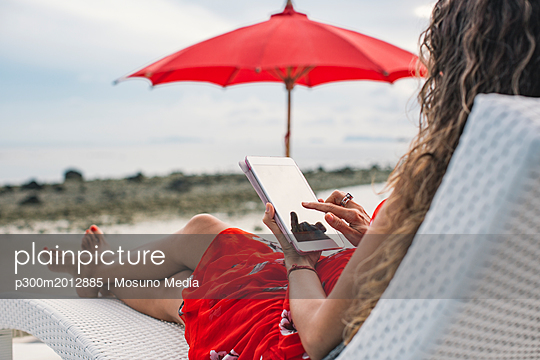 Thailand, woman using digital tablet on the beach - p300m2012885 von Mosuno Media