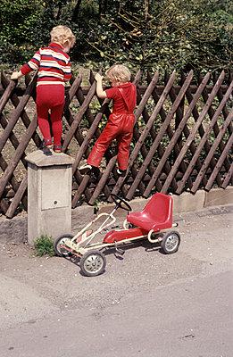 Children climbing up a fence - p236m830969 by tranquillium