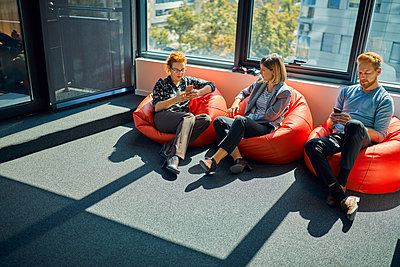 Colleagues with cell phones sitting in bean bags in office lounge - p300m2062937 by Zeljko Dangubic