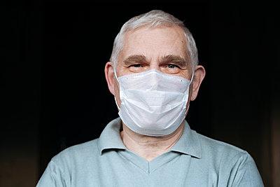 Portrait of senior man wearing a mask at home - p300m2180170 by Ekaterina Yakunina