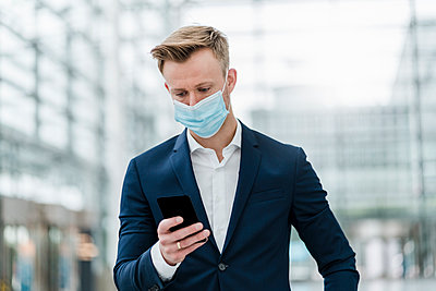 Businessman using smart phone while wearing face mask in city - p300m2206578 by Daniel Ingold