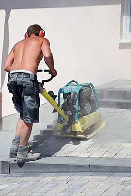 Young man paving stones with vibrator - p300m798172f by Dieter Heinemann