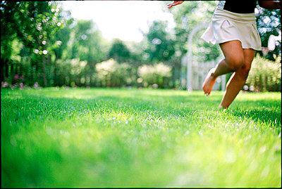 Young girl running in backyard - p3720348 by James Godman