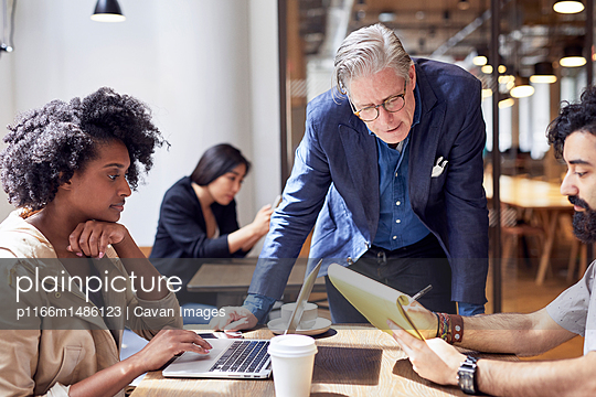 Business people working with female colleague sitting in background