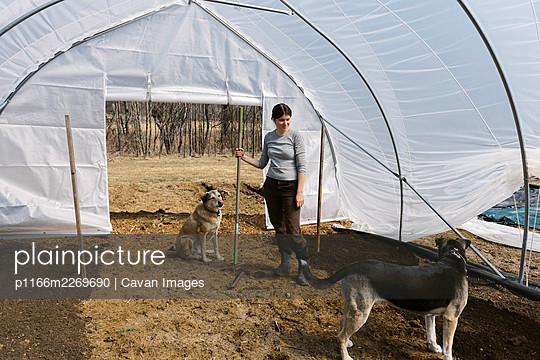 A young female farmer working in green house in the morning in spring - p1166m2269690 by Cavan Images