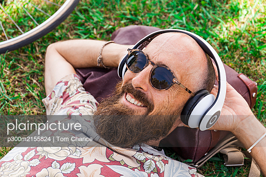 Mature man with red basecap, sunglasses and white headphones - p300m2155824 by Tom Chance