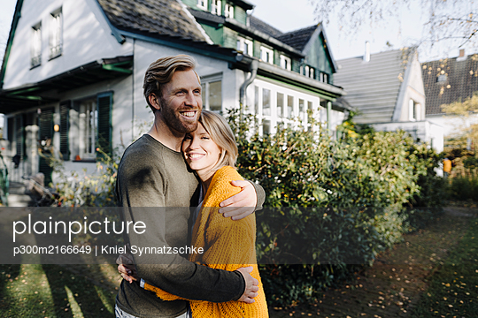 Happy couple embracing in front of their home - p300m2166649 by Kniel Synnatzschke