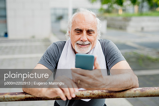 Close-up of senior man using smart phone while standing by railing - p300m2202913 by Eugenio Marongiu