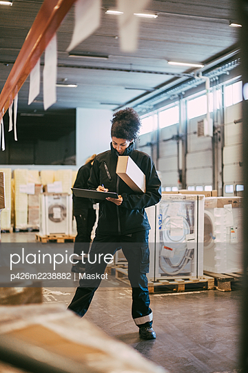 Businesswoman writing on clipboard while analyzing packages at warehouse - p426m2238882 by Maskot