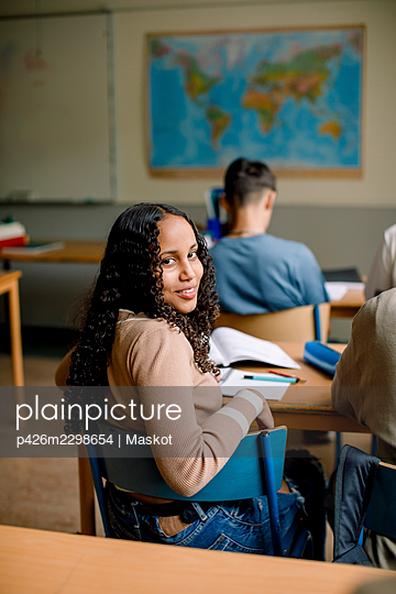 Portrait of girl siting in junior high classroom - p426m2298654 by Maskot