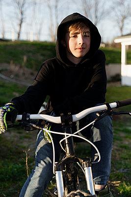 Teenage boy in black hoodie sitting on bicycle at backyard - p300m2290591 by Katharina Mikhrin