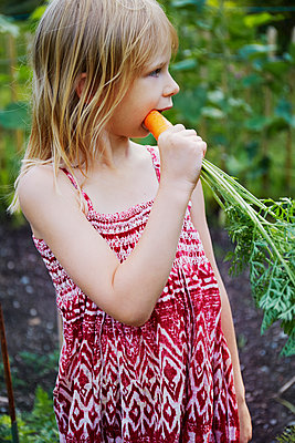 Girl eating carrot in field - p312m1121524f by Anna Kern