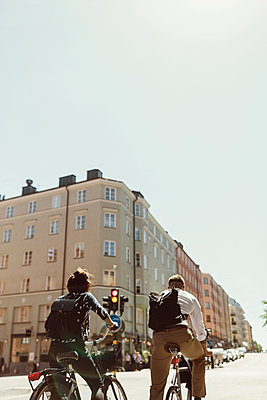 Low angle view of business colleagues riding bicycle on city street against clear sky - p426m1196691 by Maskot