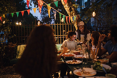 Smiling young woman showing mobile phone to female friends at table during dinner party - p426m2046185 by Maskot