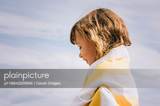 girl smiling wrapped in a striped towel at the beach - p1166m2205694 by Cavan Images
