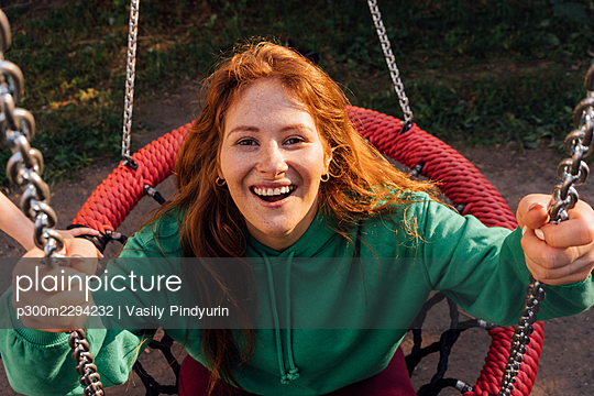 Happy young redhead woman enjoying on swing at playground - p300m2294232 by Vasily Pindyurin