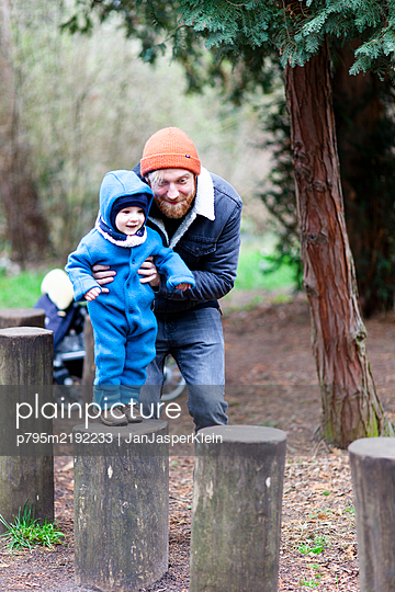 Father and son balancing on wooden pole in park - p795m2192233 by JanJasperKlein