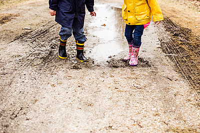 Low section of siblings playing in muddy puddle - p1166m1474030 by Cavan Images
