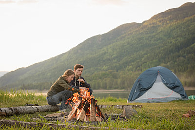 Couple sitting near campfire at campsite - p1315m1484249 by Wavebreak