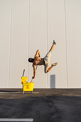 Acrobat playing with cleaning bucket and mop - p300m2012389 von VITTA GALLERY