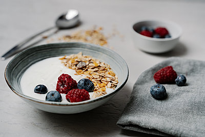 Bowl of granola with yogurt, blueberries and raspberries - p300m2166526 by Juanma Hache