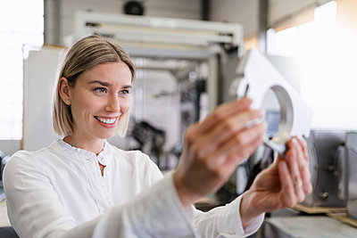 Smiling young woman holding workpiece in a factory - p300m2188344 by Daniel Ingold