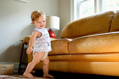 Caucasian baby boy walking near sofa - p555m1302058 by Roberto Westbrook