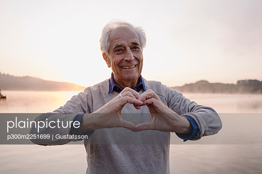 Smiling man making heart shape with hands while standing against lake - p300m2251699 by Gustafsson