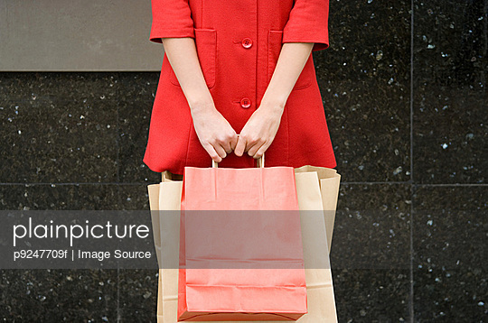 Woman holding shopping bag - p9247709f by Image Source