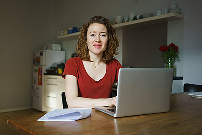 Portrait of confident woman sitting with laptop and documents at table in kitchen - p301m1579778 by Halfdark