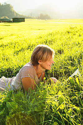 Woman reading book on grass in countryside, Sonthofen, Bayern, Germany - p429m2074948 by Brigitte Sporrer