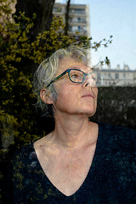 Grey-haired woman looking out of window - p445m2173638 by Marie Docher